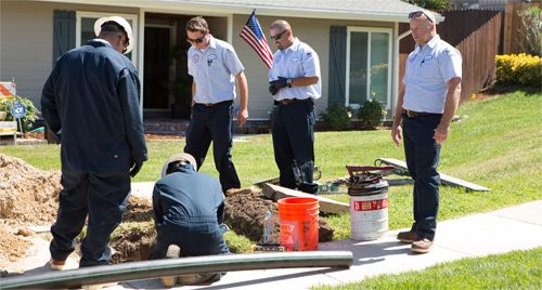 Lloyd's Plumbing technicians working in yard